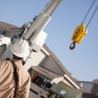 Utility Worker with Hard Hat Navigating Remote Crane. - Stock Photo