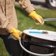 Utility Worker with Leather Gloves Opening or Sealing Oil Drum. — Foto de Stock