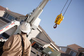 Utility Worker with Hard Hat Navigating Remote Crane. — Stock Photo