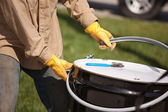 Utility Worker with Leather Gloves Opening or Sealing Oil Drum. — Stock Photo