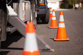 Several Orange Hazard Cones and Utility Truck in Street. — ストック写真
