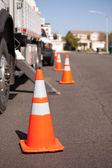 Několik kuželů oranžové nebezpečí a rozvážkový náklaďák v ulici. — Stock fotografie