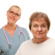 Concerned Senior Woman with Female Doctor Behind Isolated on a White Backgr — Stock Photo