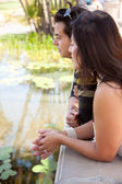 Attractive Hispanic Couple Overlook Pond Together Outdoors. — Stock Photo