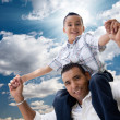 Hispanic Father and Son Having Fun Over Clouds - Stock Photo