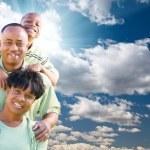 lycklig amerikansk familj över blå himmel och moln — Stockfoto
