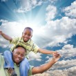 Happy African American Man with Child Over Clouds and Sky - Stock Photo
