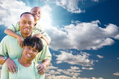 Happy African American Family Over Blue Sky and Clouds — Stock Photo