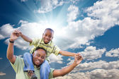 Happy African American Man with Child Over Clouds and Sky — Stock Photo