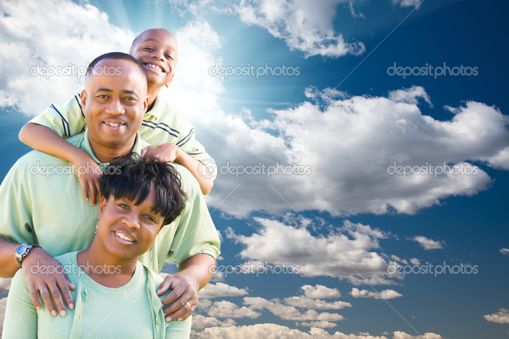 Happy African American Family Over Blue Sky, Sun Rays and Clouds. — Stock Photo #3444659