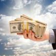 Male Hand Holding Stack of Cash Over Clouds and Sky - Stock Photo