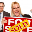 Man with Blonde Woman Holding Keys and Sold For Sale Sign — Stock Photo