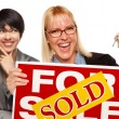 Stock Photo: Real Estate Team with WomHolding Keys and Sold For Sale Sign