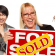 Female with Blonde Woman Holding Keys and Sold For Sale Sign — Stock Photo