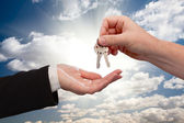 Male Handing Keys to Female Over Clouds and Rays — Stock Photo