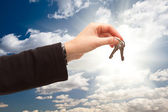 Female Holding Out Pair of Keys Over Clouds and Sky — Stock Photo