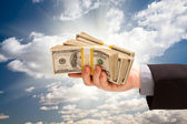 Male Hand Holding Stack of Cash Over Clouds and Sky — Stock Photo