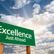 Excellence Green Road Sign Over Clouds - Stock Photo