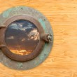 Antique Porthole with View of Sunset on Bamboo Wall — Stock Photo #3716372