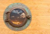 Antiguo ojo de buey con vista del atardecer en pared de bambú — Foto de Stock
