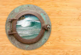 Antique Porthole with View of Crashing Waves on a Bamboo Wall Ba — Stock Photo