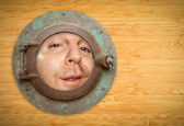 Antique Porthole on Bamboo Wall with Funky Man Looking Through — Stock Photo