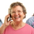 Happy Senior Woman Using Cell Phone and Doctors Behind — Stock Photo