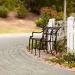 Iron Park Bench near White Picket Fence — Stock Photo #3795190