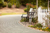 Iron Park Bench near a White Picket Fence — Stock Photo