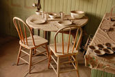 Old table and chairs covered with dust — Stock Photo
