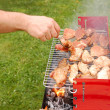 Man turning meat on a barbecue grill — Stock Photo