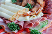 Salami and cheese rolls with vegetables — Stock Photo