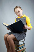 Little girl with books and glasses — Stock Photo