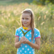 Smiling little girl with yellow flower — Stock Photo