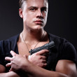 Portrait of young muscular man with gun in his hand — Stock Photo