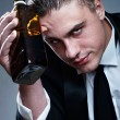Portrait of tired drunk man with whiskey bottle — Stock Photo