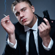 Portrait of handsome young mobster with cigarette and gun — Stock Photo #3817281