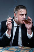 Portrait of a man in suit. Drinking whiskey and smoking cigarett — Stock Photo