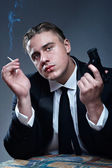 Portrait of handsome young mobster with cigarette and gun — Stock Photo