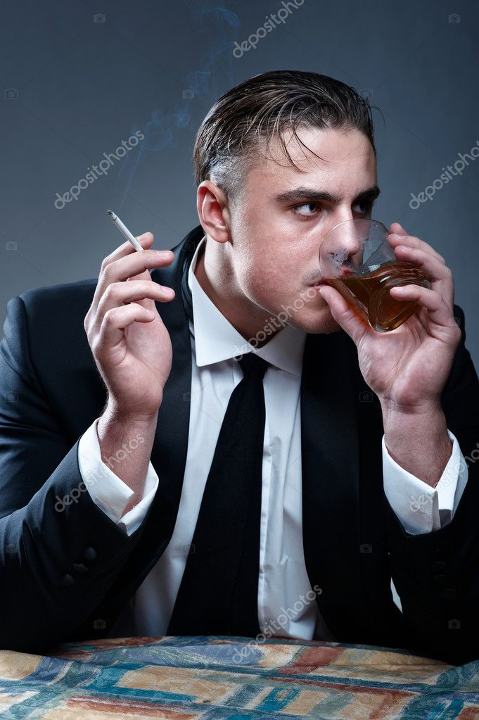 Portrait of a man in suit. Drinking whiskey and smoking cigarette — Stock Photo #3815787