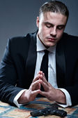 Frustrated young man in suit preparing for suicide. Black gun on — Stock Photo