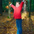 Attractive portrait of smiling little girl, throwing leaves — Stock Photo