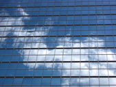 Glass wall with the reflection of sky — Stock Photo