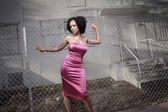 Woman posing by a fence — Stock Photo