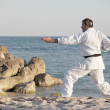 Man practicing karate on the beach — Stockfoto