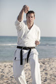 Man on the beach in a karate pose — Stock Photo