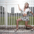 Young woman posing by the fence — Stock Photo
