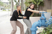 Women turning off the valve — Stock Photo