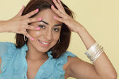 Woman smiling with her hands posed by her face — Stock Photo