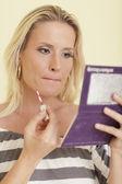Woman applying makeup — Stockfoto